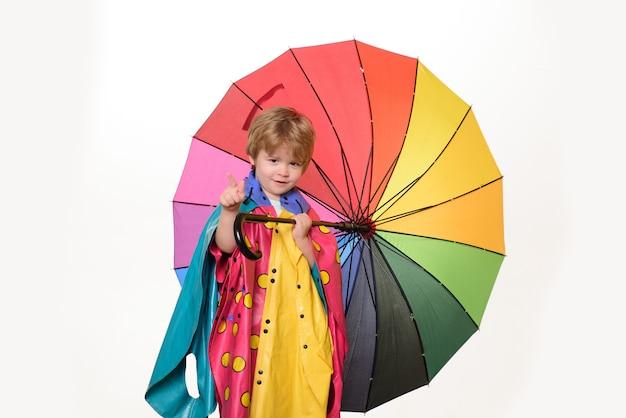 화려한 우산 비옷에 쾌활 한 소년입니다. 가을을 준비하는 잘생긴 꼬마. 구름 비 우산. 비가 개념. 귀여운 어린 소년이 가을을 준비하고 있습니다.