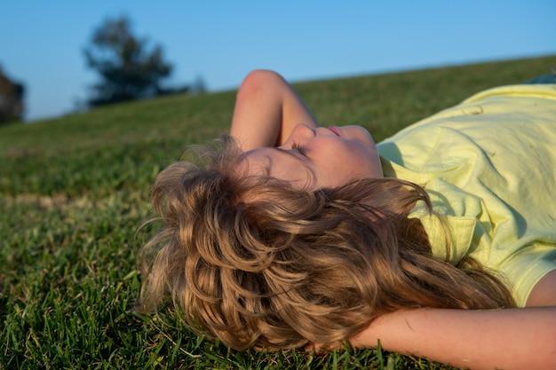 緑の芝生の上に横たわっている陽気な少年。夢を見ている子供たち。空を背景に緑の春のフィールドで遊んで幸せな子。自由と想像力の概念。