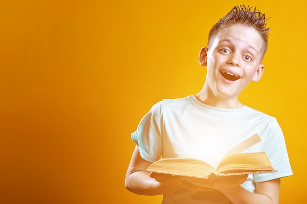 Cheerful boy in a light t-shirt holding a book on a colored