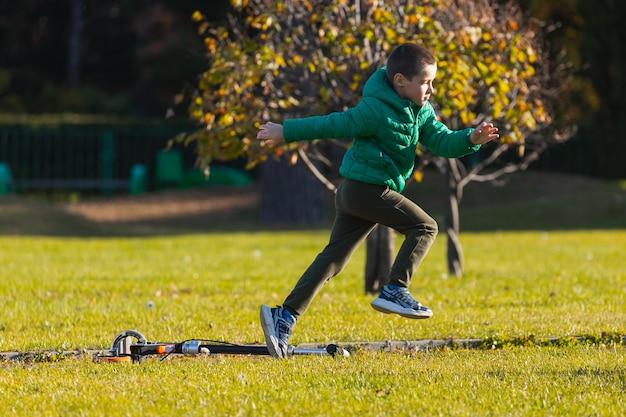 Cheerful boy  play fun, run across the green field