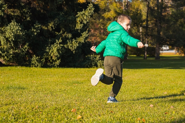 Веселый мальчик играет весело, бегает по зеленому полю в теплый осенний день