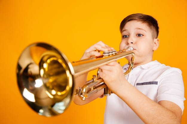 A cheerful boy plays the pipe blowing his cheeks. humor playing a wind instrument