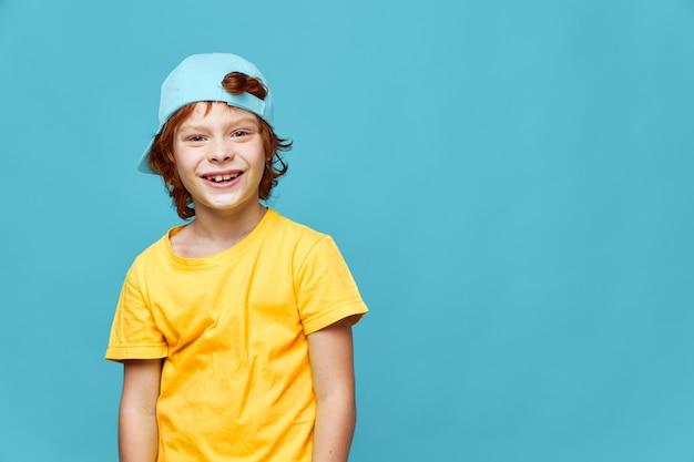 Cheerful boy red hair blue cap on his head yellow t-shirt copy space