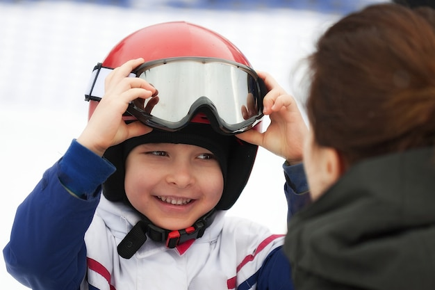 Cheerful boy in red helmet, ski goggles and white jacket smiling to his mother. winter sports, young skier, snowy background