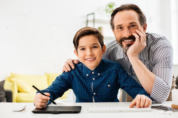 グラフィックタブレット上のスタイラスでタブレットに座っている陽気な男の子と彼の幸せな父は彼の近くに立って笑っている