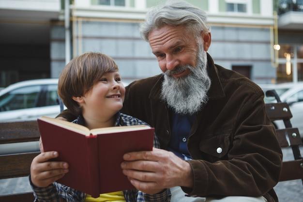 一緒に本を読みながらおじいちゃんに微笑んでいる元気な男の子