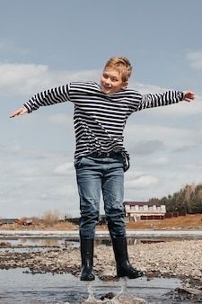 A cheerful boy in a striped vest and rubber boots jumps in the water on the river bank.