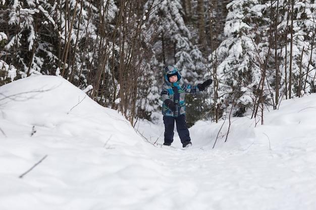 Cheerful boy walks in the winter woods