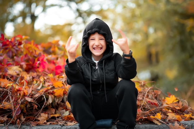 Cheerful boy wearing black clothes sits on the border against the background of an autumn bush and shows gestures