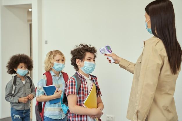 얼굴 마스크를 쓴 쾌활한 소년이 선생님이 체온을 측정하는 모습을 지켜보고 있습니다.