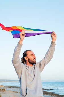 ビーチでlgbtqレインボーフラッグを持つ陽気な少年。青空に対して虹色の旗を保持している若い男