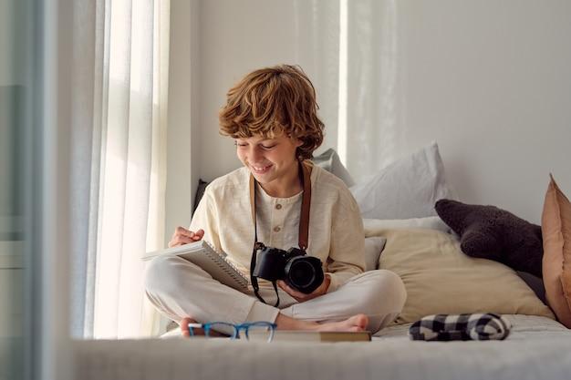 Веселый мальчик с фотоаппаратом, писать в тетрадке на кровати