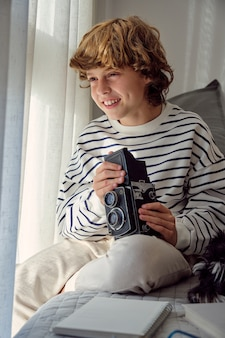 Cheerful boy with retro photo camera on bed