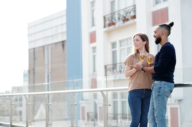 Cheerful boyfriend and girlfriend standing on rooftop of apartment building, drinking white wine and enjoying city view