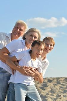 ビーチで祖父母と陽気な男の子 Premium写真