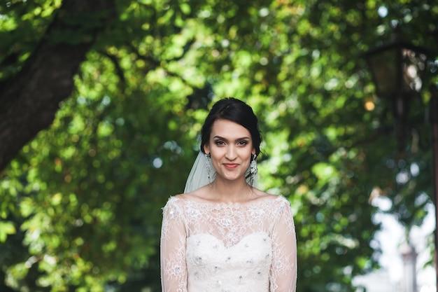 カメラで幸せに眺めている朗らかな花嫁