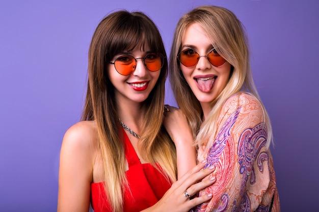 かわいい姉妹の親友の女性の陽気で明るいポジティブな肖像画。紫の空間でポーズをとって、舌と笑顔、抱擁、家族を示しています。