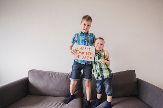 母の日を祝うための看板を持つ陽気な兄弟