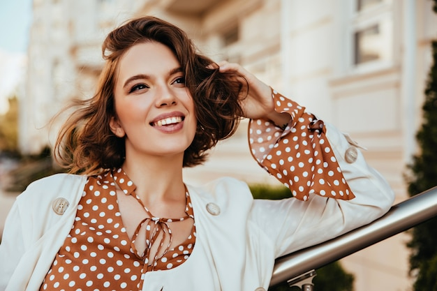 周りを見回すエレガントな服装の陽気な茶色の髪の女性。ぼやけた街に立っている短い髪型の官能的な魅力的な女の子の屋外の肖像画