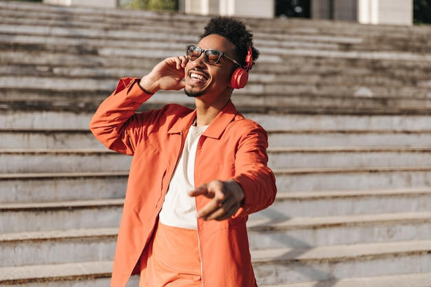 Cheerful brunet young man in orange jacket, colorful t-shirt and sunglasses sings, dances and listens to music in headphones outside