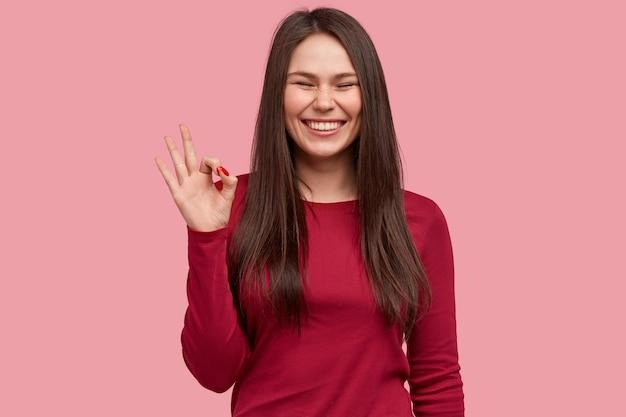 쾌활한 갈색 머리 아시아 여성은 손으로 괜찮은 몸짓을하고, 넓게 미소를 짓고, 얼굴에 주근깨가 있고, 그녀의 동의를 보여주고, 빨간 옷을 입습니다.