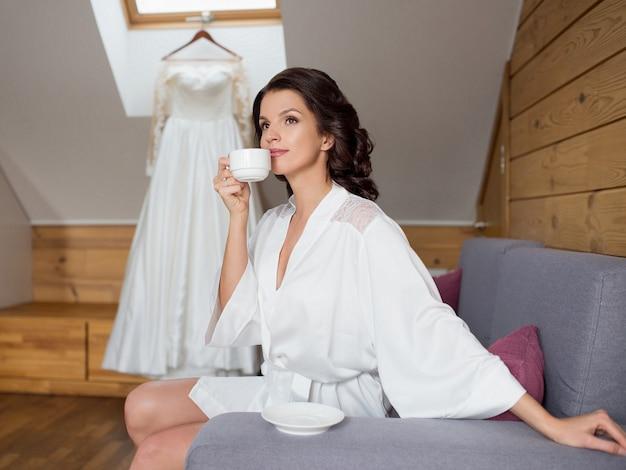Cheerful brunette bride woman in white silk robe drinking coffee on wedding dress background