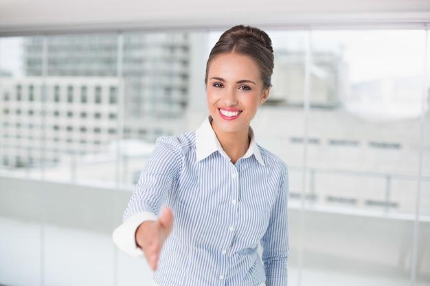 Cheerful brunette businesswoman standing for hand shake
