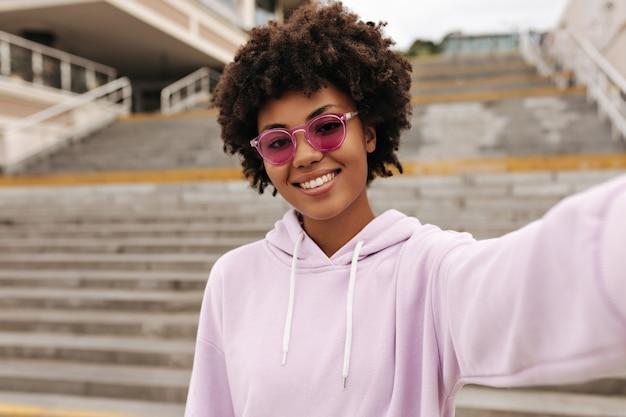 Жизнерадостная брюнетка кудрявая карие женщина в розовых очках и фиолетовой толстовке с капюшоном улыбается и делает селфи возле лестницы на улице