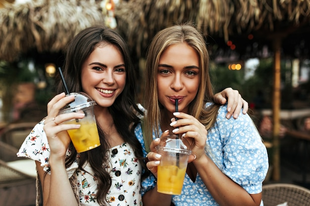 Cheerful brunette curly woman in floral trendy blouse and tanned blonde girl in blue top smile and holds lemonade glasses outside