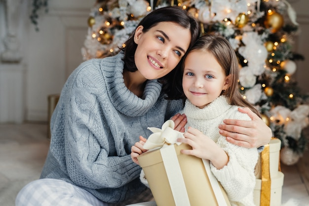 Cheerful brunette female leans at her daugter, embraces her, presents gift box, being in living room near decorated new year tree. glad family: mother and daughter in warm sweaters celebrate christmas