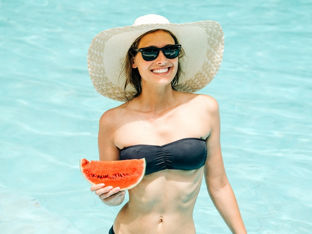 Cheerful brunette girl in a black bikini holding a watermelon in her hands and smiling
