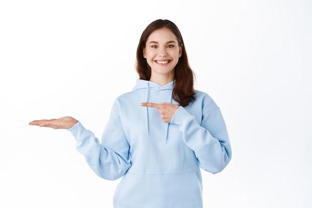 쾌활한 브루네트 소녀가 카피스페이스를 들고 손바닥을 가리키고, 그녀의 손에 전시품을 보여주고, 흰 벽에 기대어 서 있다