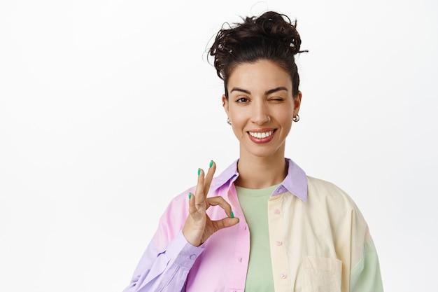 Веселая брюнетка, довольная улыбающаяся девушка, показывающая нулевой знак «хорошо», жест «ок» и подмигивание, уверяющая, что все под контролем, все в порядке, довольная стоя на белом.