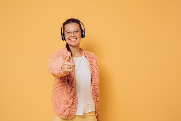 Cheerful brunette in glasses and headphones dressed in pink sweater white blouse and yellow pants broad smiling, pointing at camera over yellow background with copy space. positive and young.