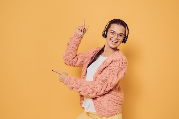Cheerful brunette in glasses and headphones dressed in pink sweater white blouse and yellow pants broad smiling, pointing at copy space over yellow background. positive and young. choose it.