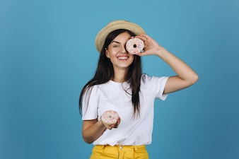Cheerful brunette has fun posing with delicious donuts in the studio
