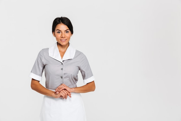 Cheerful brunette housekeeper keeping hands together while standing