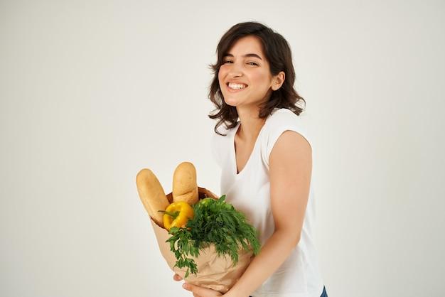 白いtシャツと彼女の頭にリンゴの食料品が入ったバッグの陽気なブルネット