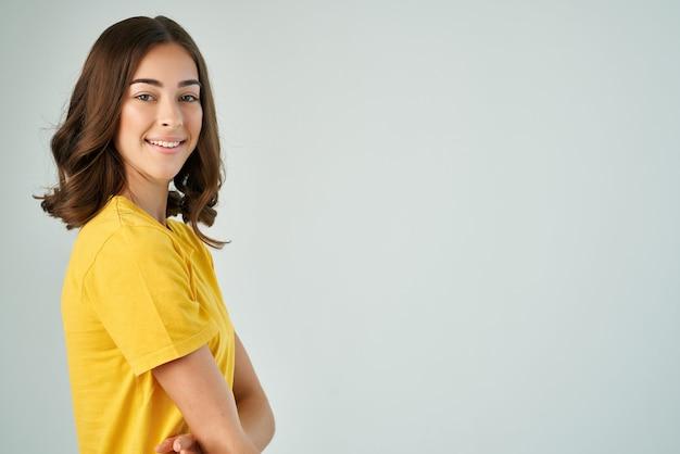 黄色のtシャツの陽気なブルネットポーズ笑顔トリミングビュー孤立した背景 Premium写真
