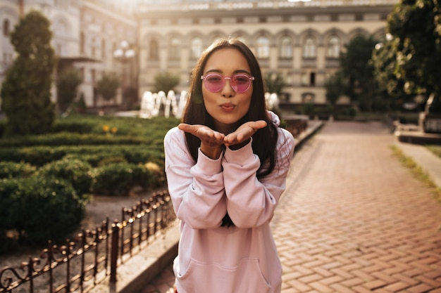 Cheerful brunette lady in colorful sunglasses and pink hoodie poses in good mood outside and blows kiss