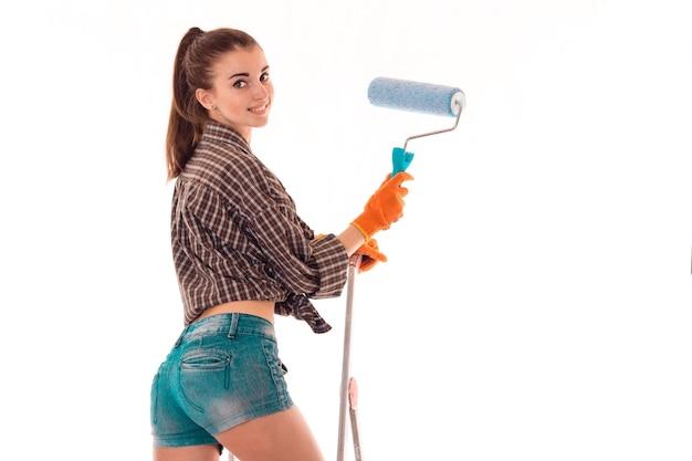 Веселая брюнетка леди делает ремонт в квартире с лестницей на белом фоне в студии