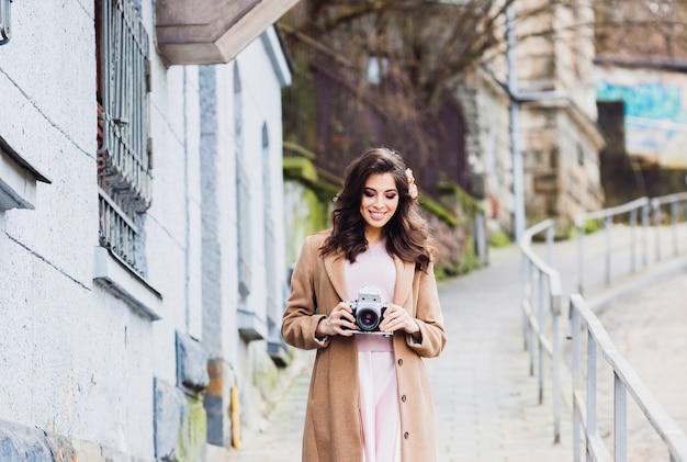 Il brunette allegro in cappotto beige lungo posa sulla via con la retro macchina fotografica