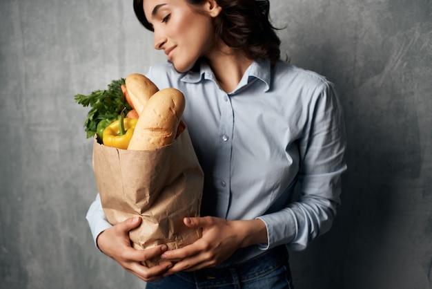 Веселая брюнетка пакет с продуктами синяя рубашка с овощами на темном фоне