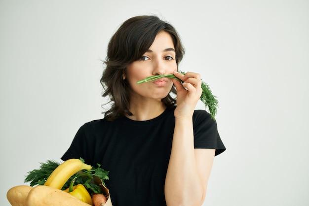 野菜の食料品の配達と陽気なブルネットのパッケージ