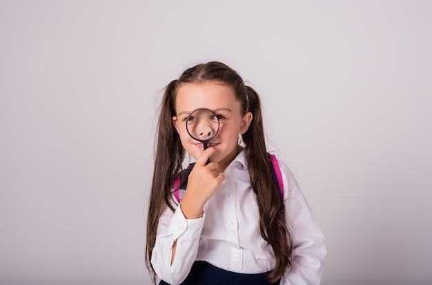 制服を着た陽気なブルネットの女子高生とテキストの場所と白い背景の上の彼女の鼻に虫眼鏡を保持します