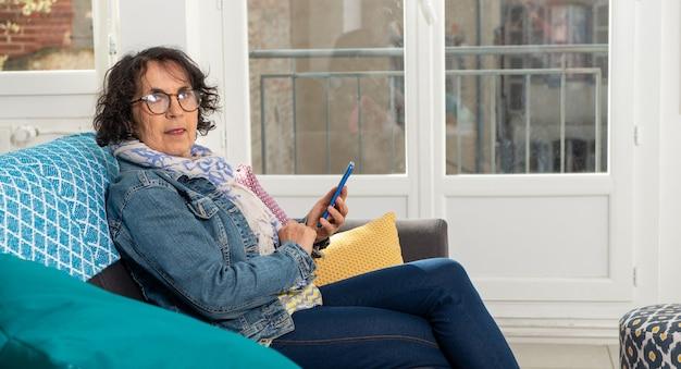ソファに座ってスマートフォンを使用して陽気なブルネットの年配の女性