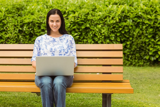 Cheerful brunette sitting on bench using laptop