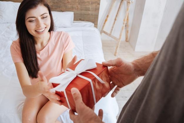 Веселая брюнетка сидит на кровати с раскинутыми руками, получая подарок от своего парня