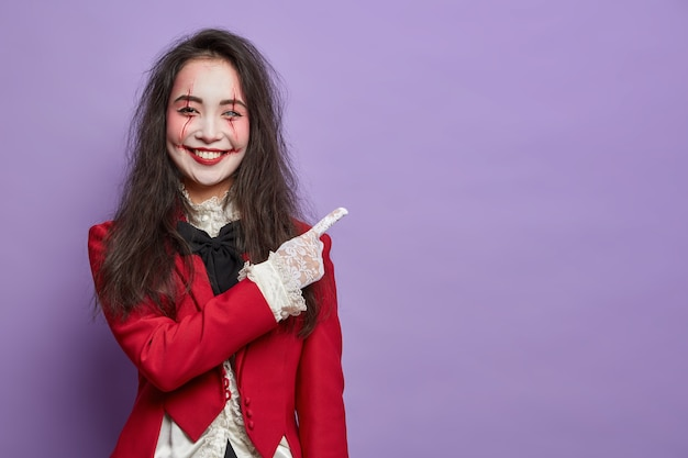 Cheerful brunette spooky woman with scars and pale face indicates at empty space dressed in carnival costume shows direction against purple wall. horror theme