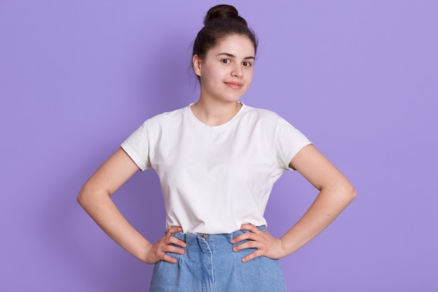 Cheerful brunette teenage girl with hair bun posing against lilac wall